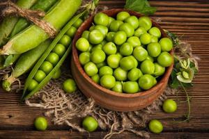 Fresh organic green peas on a wooden background. Rustic style. photo