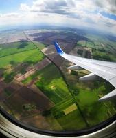 View of brown and green fields from an airplane porthole photo