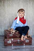 Little boy, playing with wooden planes, indoor, sitting on suitcase