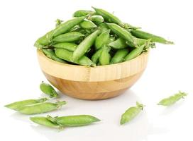 Green peas in wooden bowl isolated on white