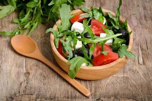 Greek salad in a wooden salad bowl on the table photo