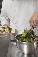 Chef preparando vegetales de hoja en cocina comercial foto