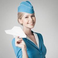 encantadora azafata con avión de papel en la mano. fondo gris foto