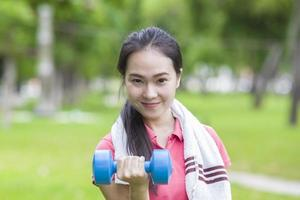 Fitness woman lifting dumbbell weight training outside photo