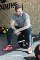 Weightlifter sitting on the barbell