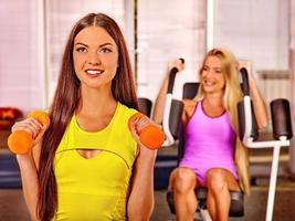 Girls holding dumbbells in sport gym