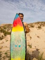 Young surfer on the beach  hides behind his colorful surfboard