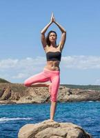 woman staying in yoga pose on stone of rocky coast photo