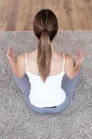 Beautiful young woman doing yoga exercises at home. photo