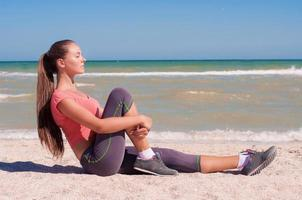 Young beautiful girl athlete playing sports on the beach photo