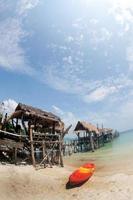 canoa na praia e ponte de madeira tradicional.
