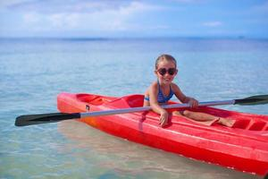 Little brave girl floating in kayak on high blue sea photo