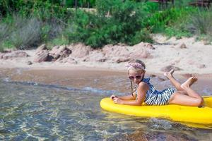 Adorable little girl kayaking during summer vacation photo
