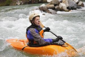 junges männliches Wildwasserkajakfahren