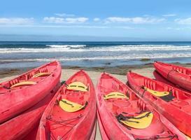 Grupo de canoas de fibra de vidrio rojo brillante apiladas en la playa de arena