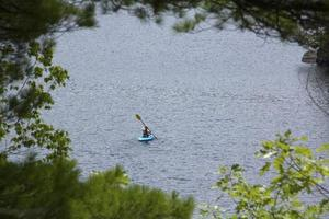 Young woman in kayak, water in Sunapee, New Hampshire, horizonta