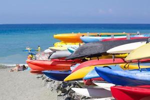 ¡Barcos de colores brillantes apilados en la playa listos para la acción!