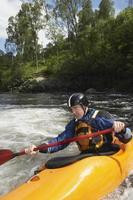 Man kayaking in river photo