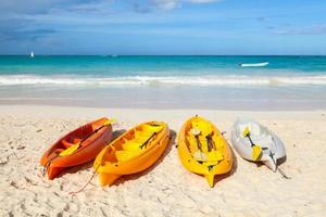 Colorful plastic kayaks lay on empty sandy beach