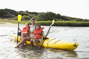 adolescente con niñas sentadas en kayak