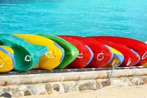 Range of colorful canoes on a beach, blue water background