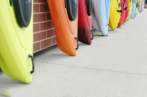 Kayaks Leaning On A Red Brick Wall On Street photo