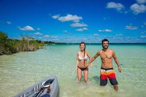 Beautiful couple in love kayaking at tranquil Bacalar lake. Rivi
