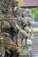Row of stone sculptures at Tirtagangga Water Palace