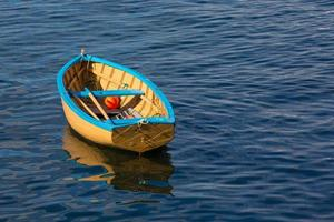 Small row boat sitting calmly in a harbor