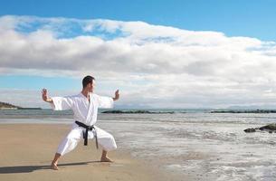 um homem praticando karatê na praia