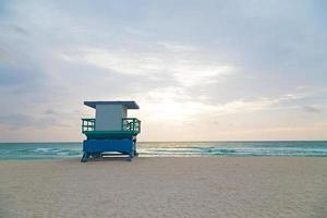 praia vazia com cabine de salva-vidas ao nascer do sol.