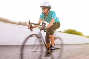 Joven atleta femenina de carreras en bicicleta. imagen borrosa de movimiento foto