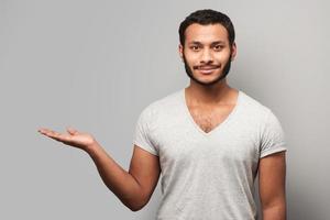 homme de race mixte souriant pointant de côté