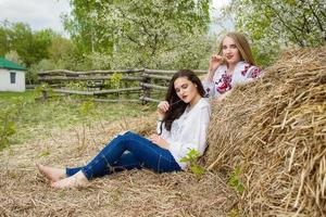 Two young beautiful  girls with long hair in Ukrainian blouses