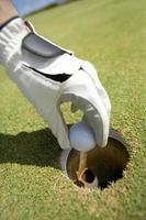 mano de golfista con pelota foto