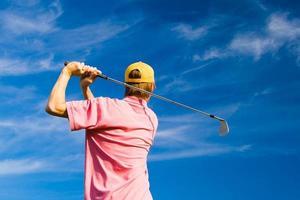 Golfista masculino sobre fondo de cielo azul de verano