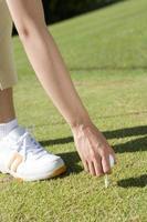 Female golfer setting up a tee photo