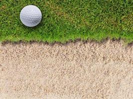 Golf ball on green grass near sand trap