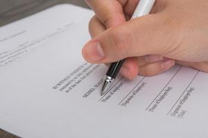 Close up of hand completing an employment application form photo