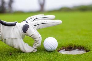 La mano del hombre poniendo la pelota de golf en el hoyo en curso foto