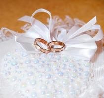 Gold wedding rings on the pincushion. Soft focus photo