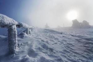 paisaje de invierno y barandas de madera con nieve helada en niebla en niebla
