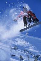 Snowboarder in der Luft mit Schneepulver dahinter