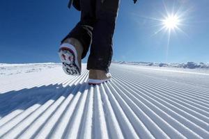 Snowboarder camina a lo largo del rastro de nieve preparado en las montañas