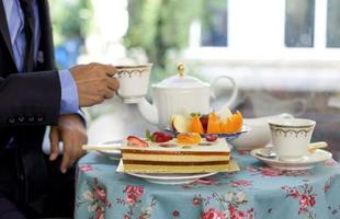 Businessman having  tea with cake and fresh fruit