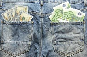 Euro and Dollar banknotes in jeans back pockets