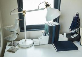 work table with lamp,pencil, books in a home photo