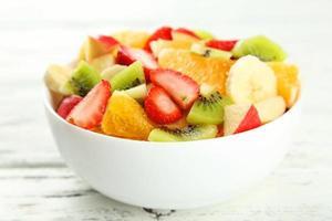 Ensalada de fruta fresca sobre fondo blanco de madera