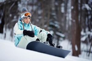 chica con snowboard tomando un descanso foto