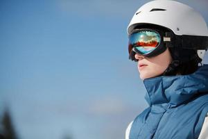 female snowboarder against sun and sky photo